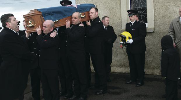 Firefighter Nial Hamilton's helmet is carried by a colleague as his coffin is taken from St Michael's Church, Co Fermanagh