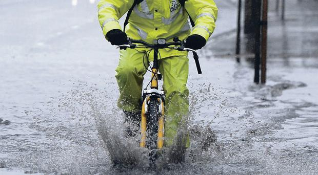 A cyclist struggles through the rain and puddles in Belfast, and (right) a woman shopper battles with her umbrella