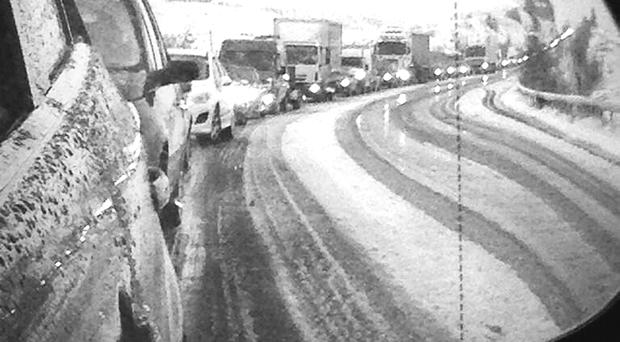 The view through a wing mirror of the queue on the Glenshane Pass, and a driver gets out of his lorry as traffic comes to a halt