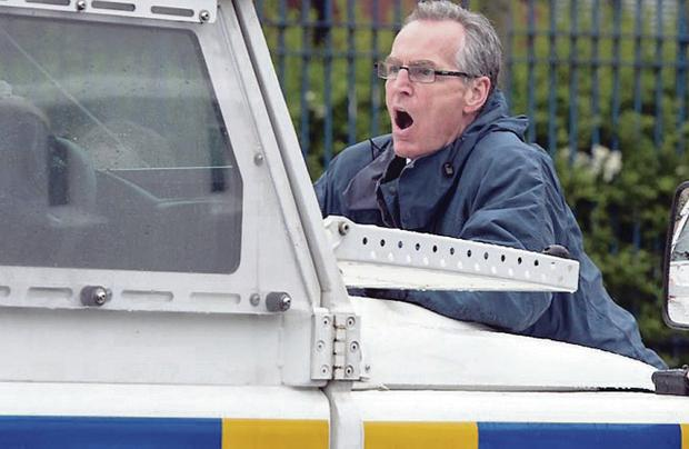 Sinn Fein's Gerry Kelly on the bonnet of the police Land Rover