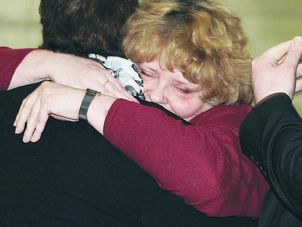Relatives of victims comfort each other at Stormont