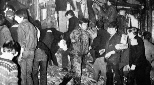 Rescuers, soldiers and civilians dig with bare hands in the still smoking rubble of McGurk's bar.