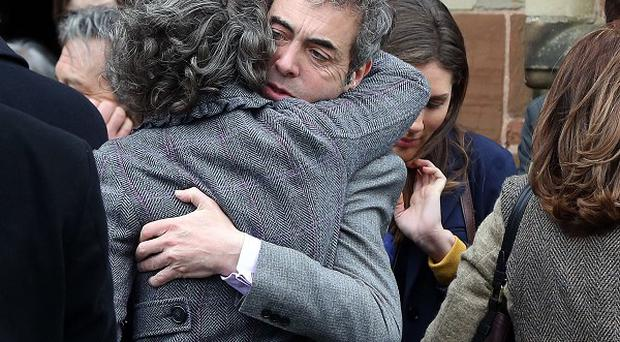 Jimmy Nesbitt, left, hugs Robina, the wife of Jimmy Ellis following his funeral which took place at St Mark's Church on Holywood Road, east Belfast.