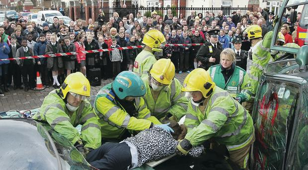 Schoolchildren watch a dramatisation of the aftermath of a car crash with actors used to play the part of those involved in the accident at St Peter's Square, Belfast