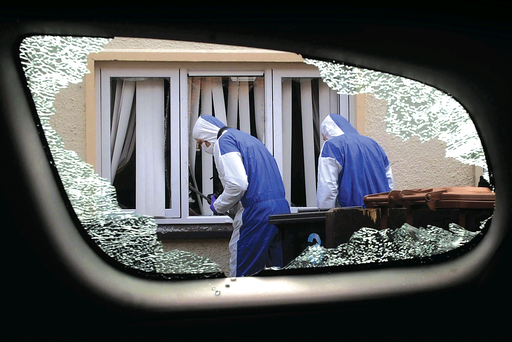 Forensic experts glimpsed through the smashed window of a car as they comb the scene in Larne's Ferris Avenue for evidence