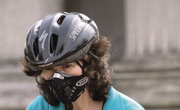 A cyclist in wears an anti-pollution mask