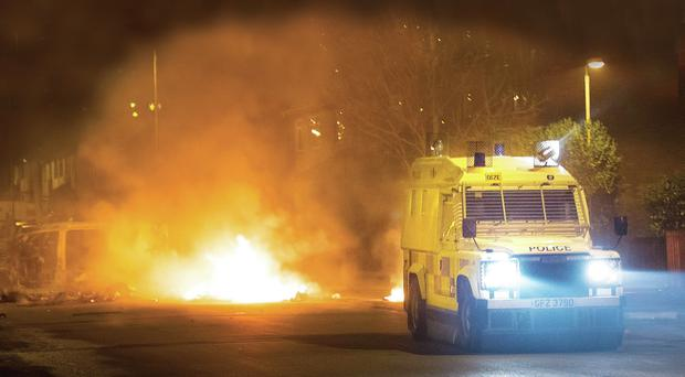 A police Land Rover passes a burning barricade in Carrickfergus