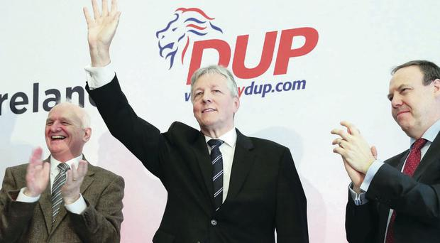 Peter Robinson salutes the audience flanked by MPs William McCrea and Nigel Dodds