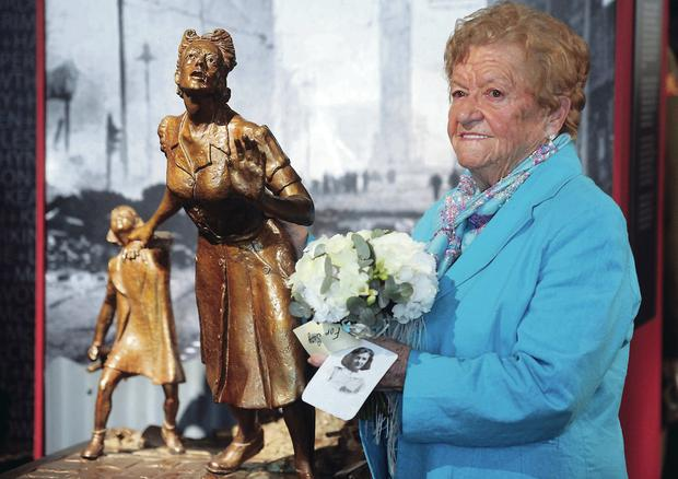 Brigid Henry with a posy and a photo of her sister Suzie at the 73rd anniversary of the Belfast Blitz at the Northern Ireland War Memorial Building.