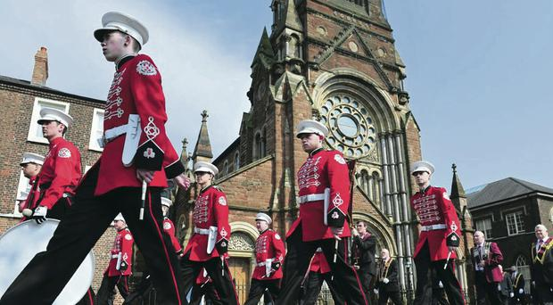 A flute band passes St Patrick's Church on Donegall Street in Belfast
