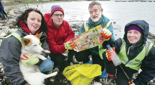 Tania McFaul (and Brodie the dog), Jonathan Mitchell, David Quinney-Mee and Aisling Gribbin (Keep Northern Ireland Beautiful) with the message in the bottle thrown from an Icelandic cargo ship in 2005 that was found on Church Bay beach