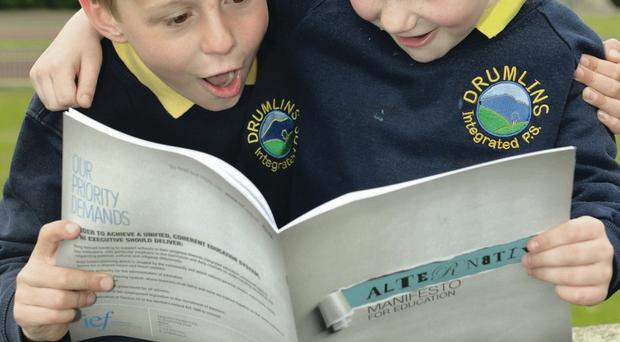 Drumlins Integrated Primary School pupils Caleb Doherty and Charley Stokes reading the Integrated Education Fund Alternative Manifesto For Education yesterday