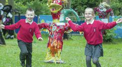 Corey Morgan (8) and Nataliah Dzieciatko (8) run for their lives from the scarecrows at Garden Show Ireland