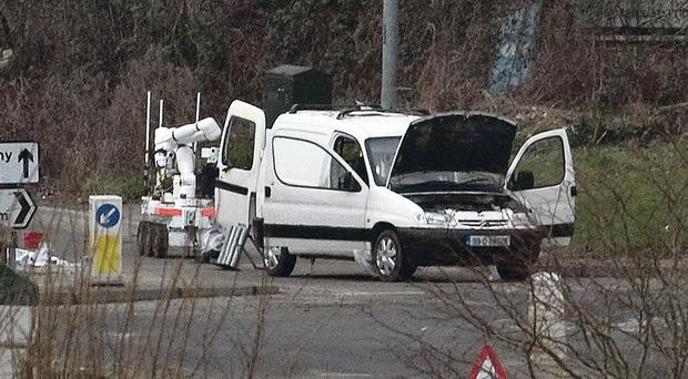 An Army robot examines the van in Derry last year. The mortar tubes can be seen on the ground beside the van