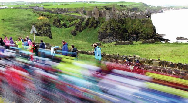 Giro riders whizzing past the imposing Dunluce Castle