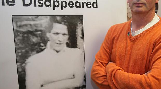 Michael McConville poses with a picture of his murdered mother, Jean.