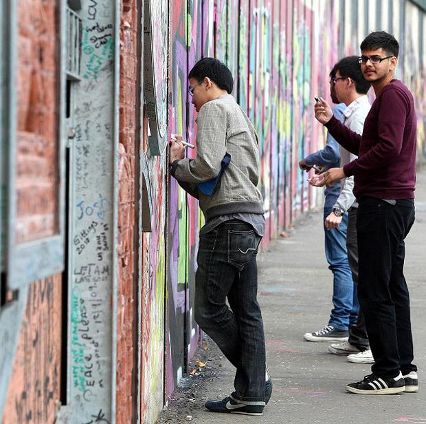 Tourists write messages on the Peace Wall in Belfast