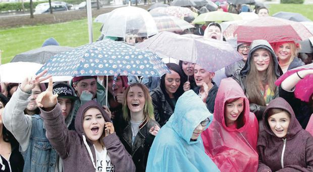 Fans brave the rain as they queue for Miley Cyrus's concert at the Odyssey last night
