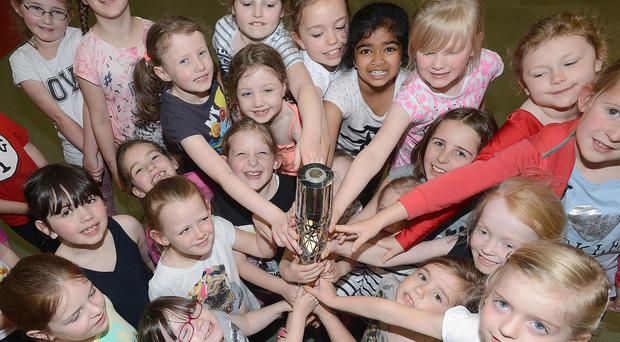 Antrim Forum Gymnastics Club members get their hands on the Queen's Relay Baton during its visit to Antrim yesterday