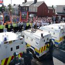 PSNI officers stop Orangemen and loyalists from marching along the Woodvale Road during last year's Twelfth
