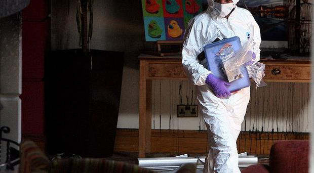 A police forensic expert in the reception area of the Everglades Hotel in the Prehen area of Derry