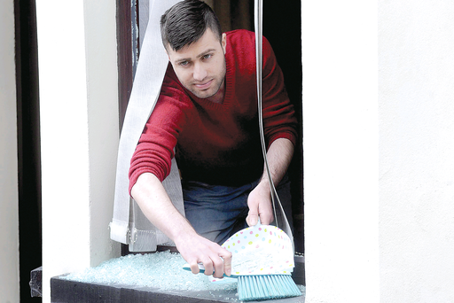 Muhammad Asif Khattak clears up after his north Belfast home was targeted by racists