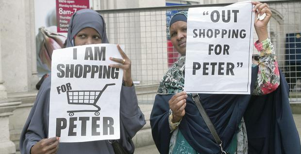 Two women join the I am Shopping for Peter flash mob on Royal Avenue