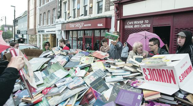 Passing shoppers in Londonderry help themselves to some of the thousands of books dumped in a skip outside the Bookworm shop which has closed down