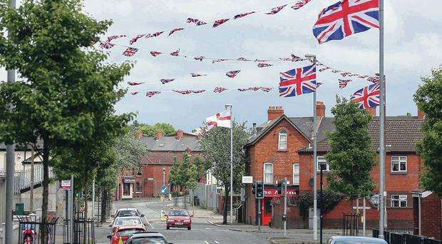 Union flags and bunting on streets in Belfast this week. Putting them up in mixed areas could now be an offence