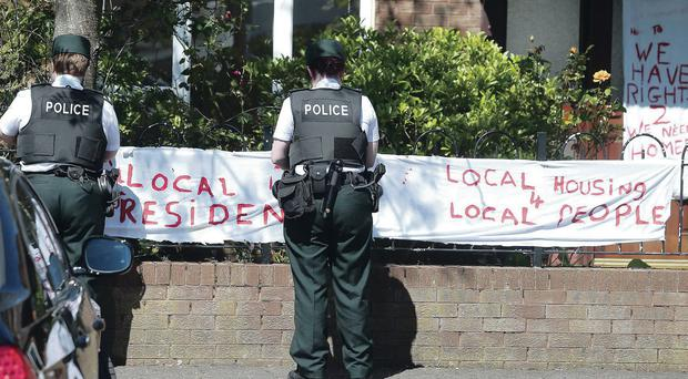 PSNI officers yesterday remove banners put up by protesters outside the house at Glenuce Drive in east Belfast allocated to Michael Abiona