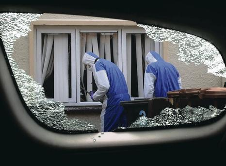 Forensic officers examine a house in Larne after the March disturbances