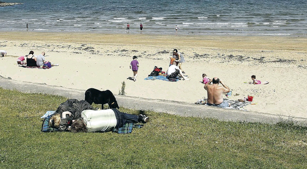 People soak up the sun at Helen's Bay