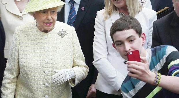 A teenager tries to take a selfie with Queen Elizabeth II during her tour of St George's Market in Belfast