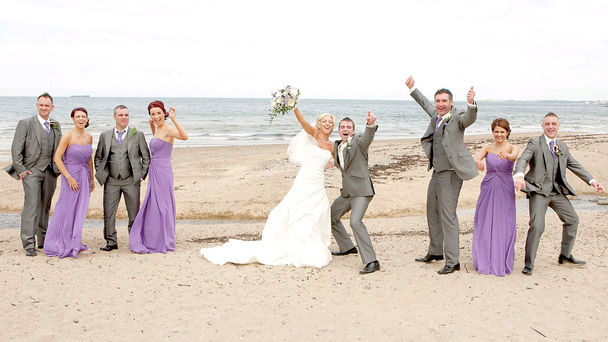 Kerrie and Robert Macauley celebrate on the beach with their bridal party. Pictures by Darron Mark Photography