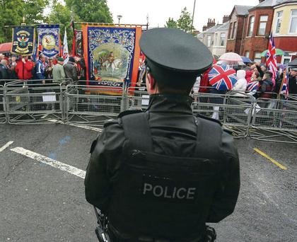 A police officer looks on as a loyalist parade marches to the barricade at Woodvale last month