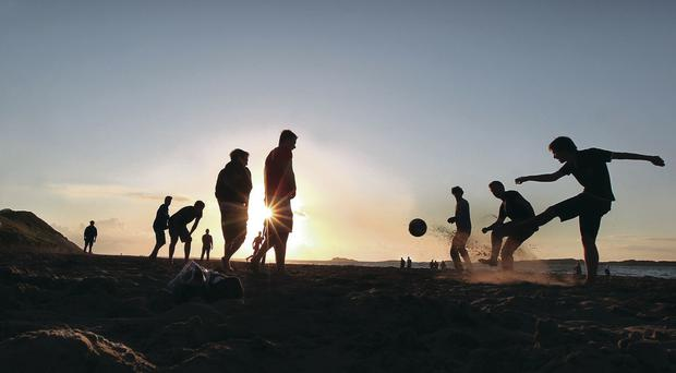 Footy on the beach in the evening sun at White Rocks strand close to Dunluce Castle in Co Antrim