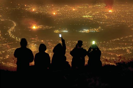 People take photographs with their phones of bonfires burning across Belfast from Cavehill