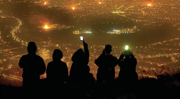 Loyalist youths take photographs from Cavehill with their mobile phones of Eleventh night bonfires burning across Belfast