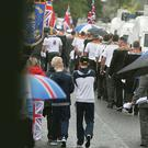 A large police presence as an Orange Order parade makes its way down Woodvale Road adjacent to the nationalist Ardoyne neighbourhood