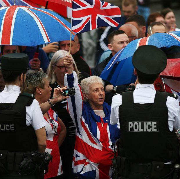 Loyalist supporters cheer on an Orange Order parade on the Crumlin Road as part of the annual Twelfth of July celebrations