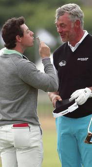 Rory McIlroy takes a £20 note after winning a bet with Darren Clarke after practice before the start of The Open at Royal Liverpool
