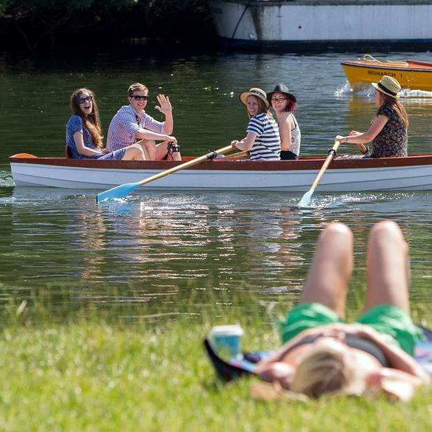 People sunbathe on the bank of the River Thames in Windsor, Berkshire, as temperatures across many southern parts of England soared