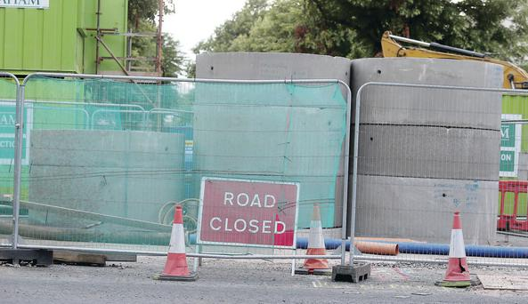 Workmen's barriers on Belfast's Ravenhill Road yesterday after large voids were discovered underneath its surface