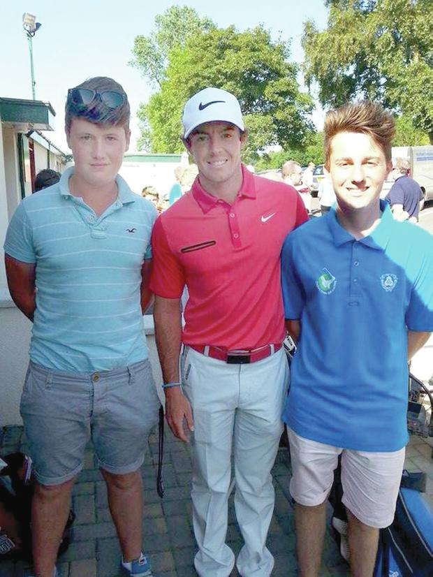 Open champion Rory McIlroy meeting young fans Chris Quinn and PJ Rowan during his visit to Holywood Golf Club yesterday