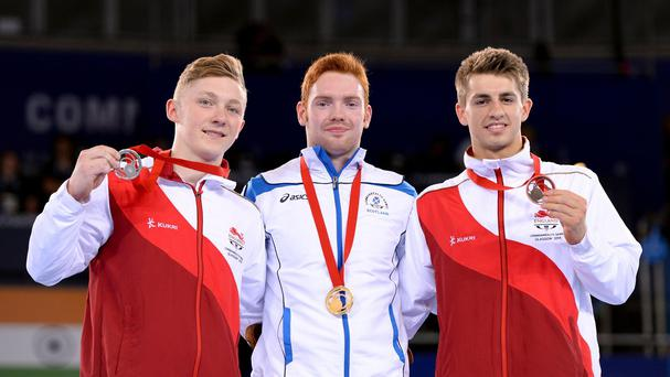 Silver medalist England's Nile Wilson, gold medalist Scotland's Daniel Purvis and bronze medalist England's Max Whitlock after the Men's Parallel Bars Final