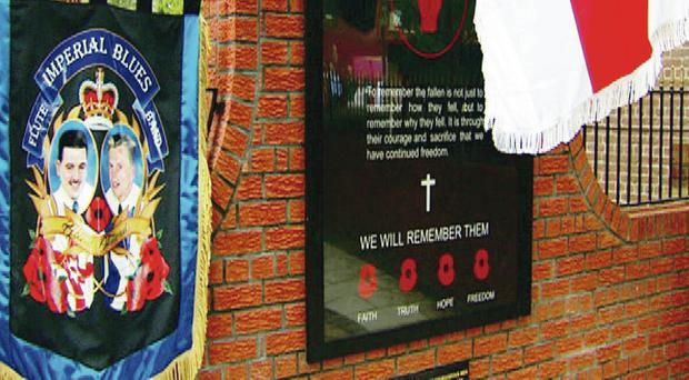 The plaque and banner bearing the names of five paramilitaries that were placed beside the permanent tribute