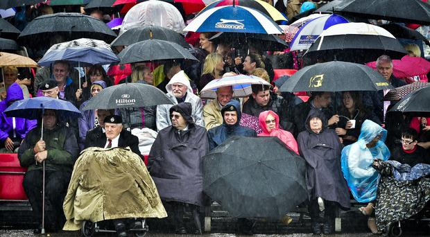 People shelter from the rain as very heavy shower passes over Tidworth, Wiltshire
