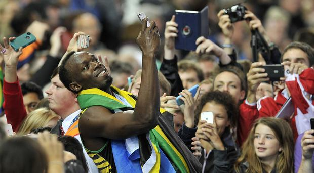 Usain Bolt takes a selfie with fans after winning the Men's 4x100m Relay at Hampden Park