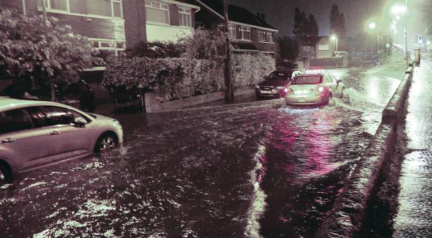 A motorist drives down the flooded Finaghy Road North in south Belfast