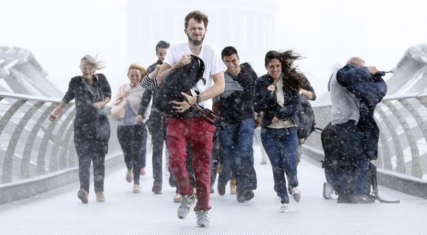 Pedestrians dash through torrential rain along the Millennium Bridge, Southwark, London, as the remnants of Hurricane Bertha swept across parts of the country.